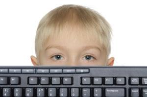 Little boy looks out keyboard